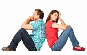 Side view of mature couple sitting back to back after a conflict. Horizontal shot. Isolated on white.